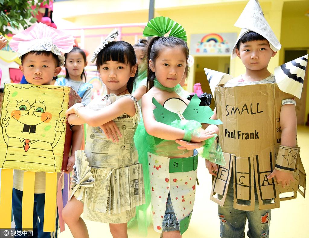 """幼儿园开展""""环保时装秀""""主题活动,孩子们身着由旧报纸,塑料袋,纸盒等"""